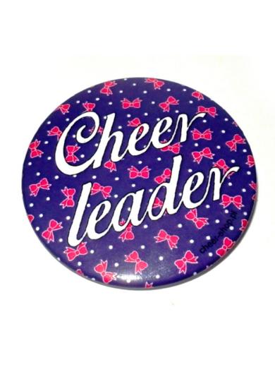 urocza fioletowa przypinka z kokardkami i napisem cheerleader